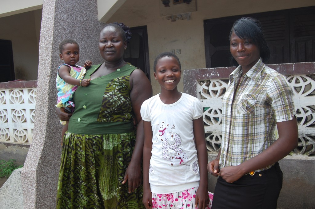 Bernice stands smiling with her family at home
