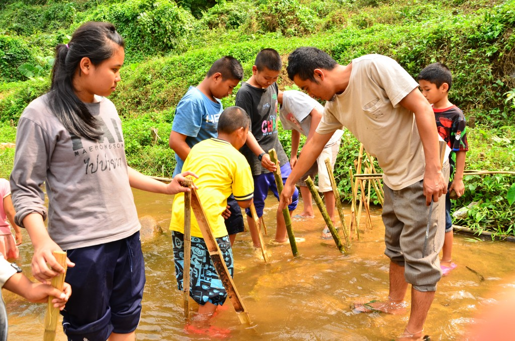 Project worker and students standing in river with Bamboo sticks in hand