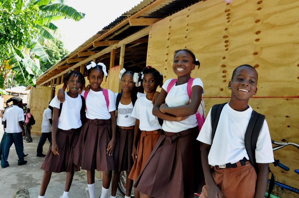 Children smile outside classroom