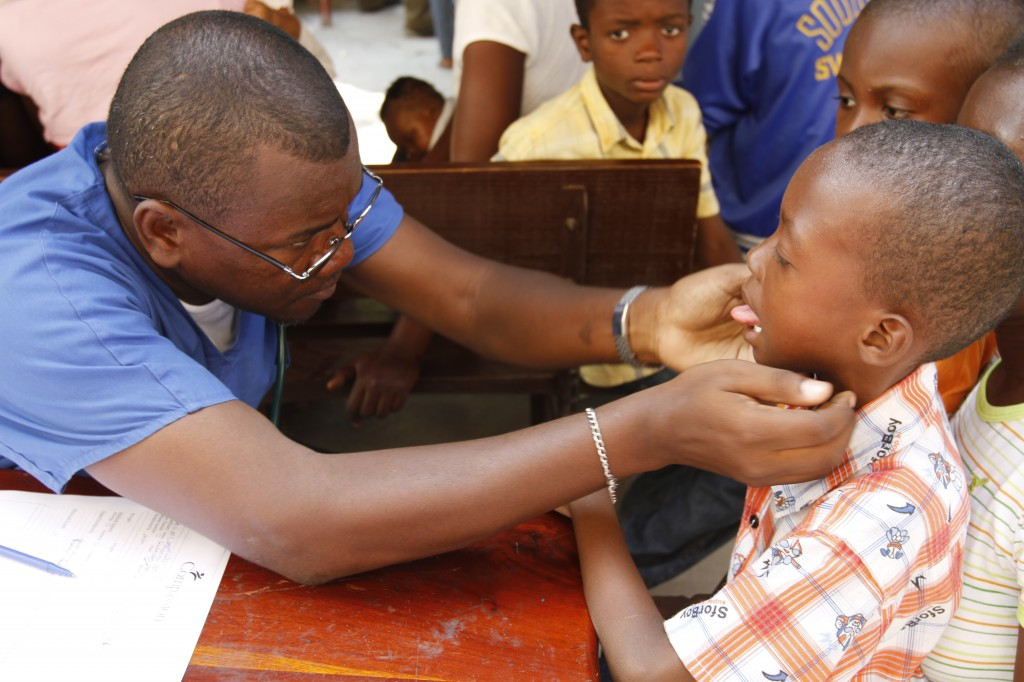 Medical team member checking a boy's mouth
