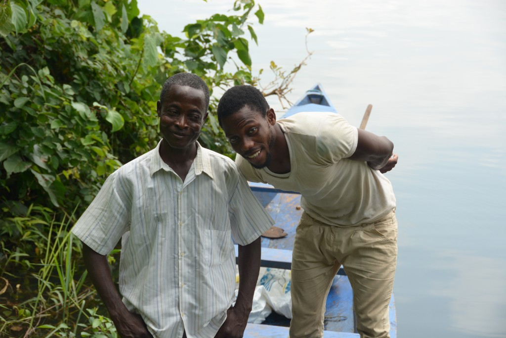 William Gasese with his friend and co worker Kofi, pose smiling together outside near a lake and boat