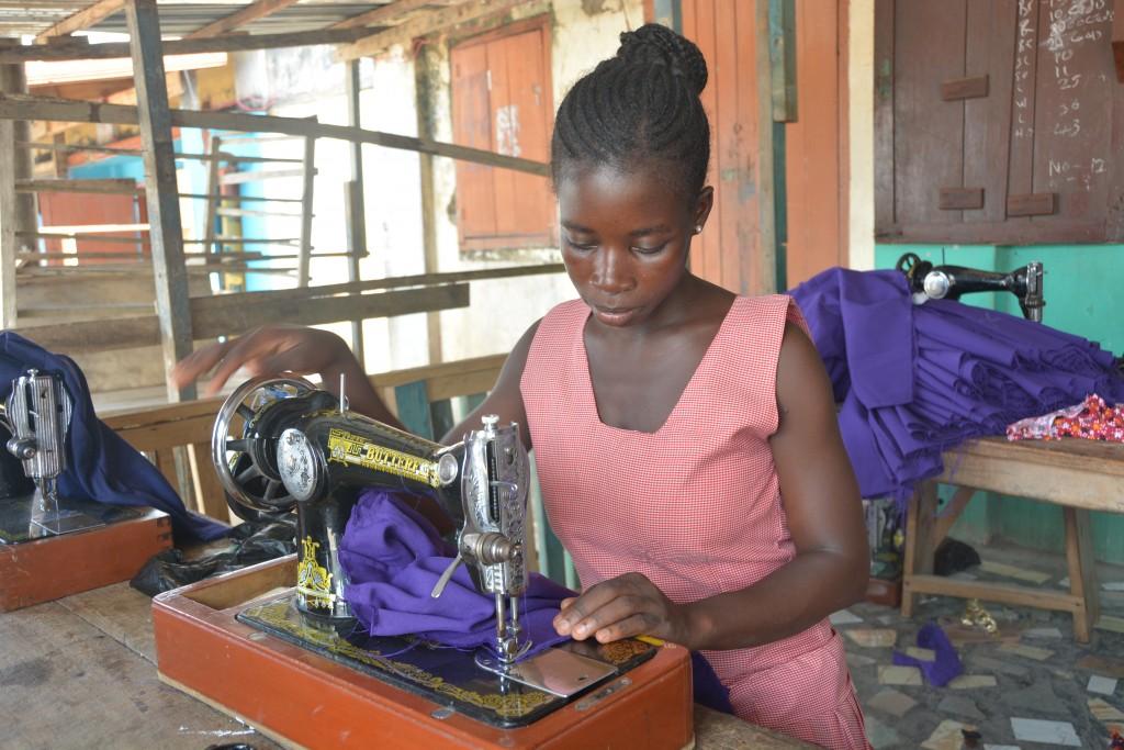 Lovintina sews purple fabric at project using a sewing machine