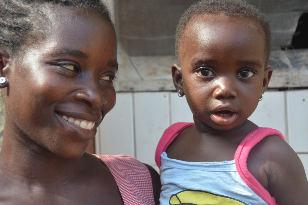 Lovintina smiles looking at her daughter in a close-up outside her home