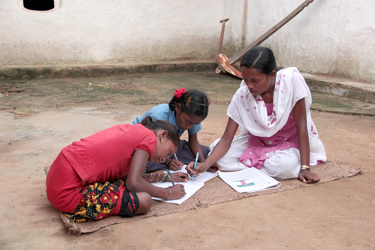 Compassion's Sensitive Messaging Standards apply to this asset for external usage. See Compassion's Communications Manual (p. 22-26)https://maxplus.compassion.com/viewpicture.tlx?pictureid=22119320320for the standards. Sampatiya Kumari, a 16 year old girl, child, teenager, youth, teen, was attending the child development center happily when her parents announced she would be in an arranged marriage and have to leave the school and center. She protested against her parents demands and Compassion helped her to avoid the arranged marriage and go on to have further education and fulfill her dreams to one day be a teacher.  Sampatiya, wearing a white and pink dress, sari, sarong, sits on a the floor inside her home, bare sparse room, looking down as she helps teaches, educates, shows writing skills, homework, schoolwork, to two younger girls, sisters, siblings, one wearing a red shirt and the other a blue shirt, who are both looking down as they learn their academic educational lessons.