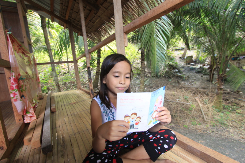 Merry Grace Legarde sits reading a letter from her sponsor at home