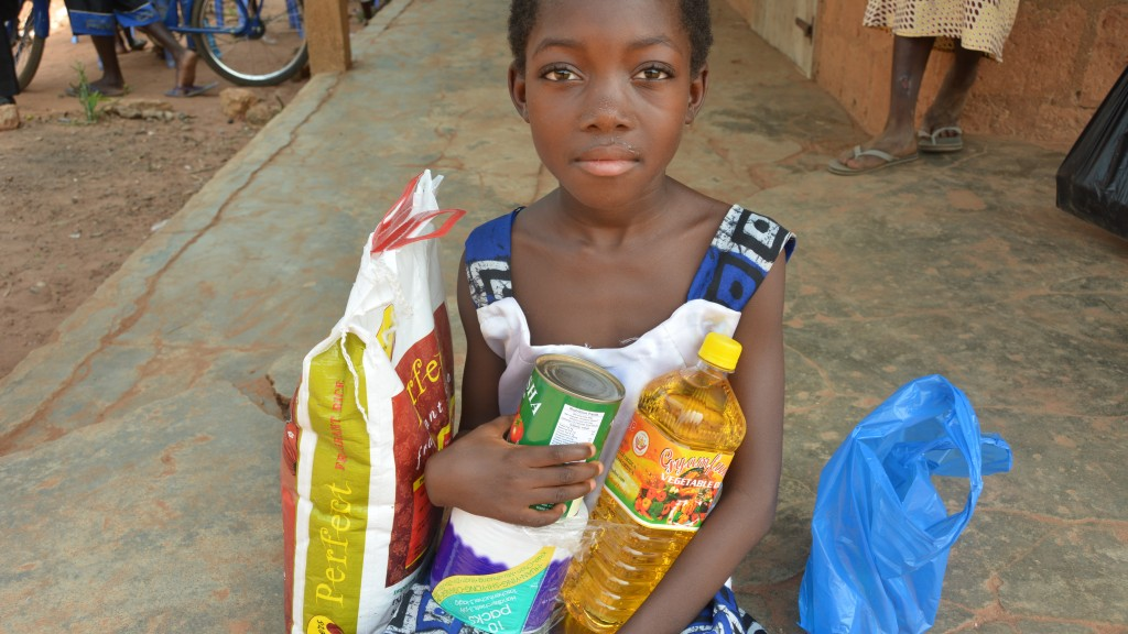 Rejoice Sicikwa Letsu happily holds her gifts of food and vegetable oil in a close-up during the special event Christmas party celebration