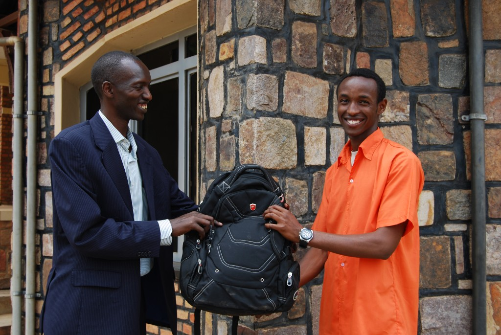 A man in a suit gives a young man a black new backpack as a gift at Christmas