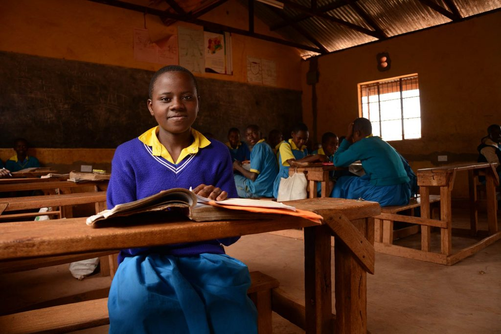 A girl sits at wooden desk in a classroom.