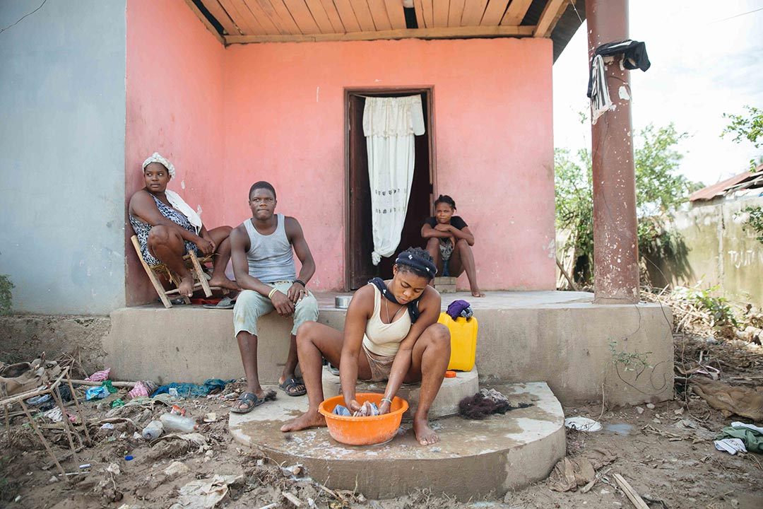 A Haitian family sits on the porch of their house surveying the damage that a recent hurricane has brought upon their neighbourhood.