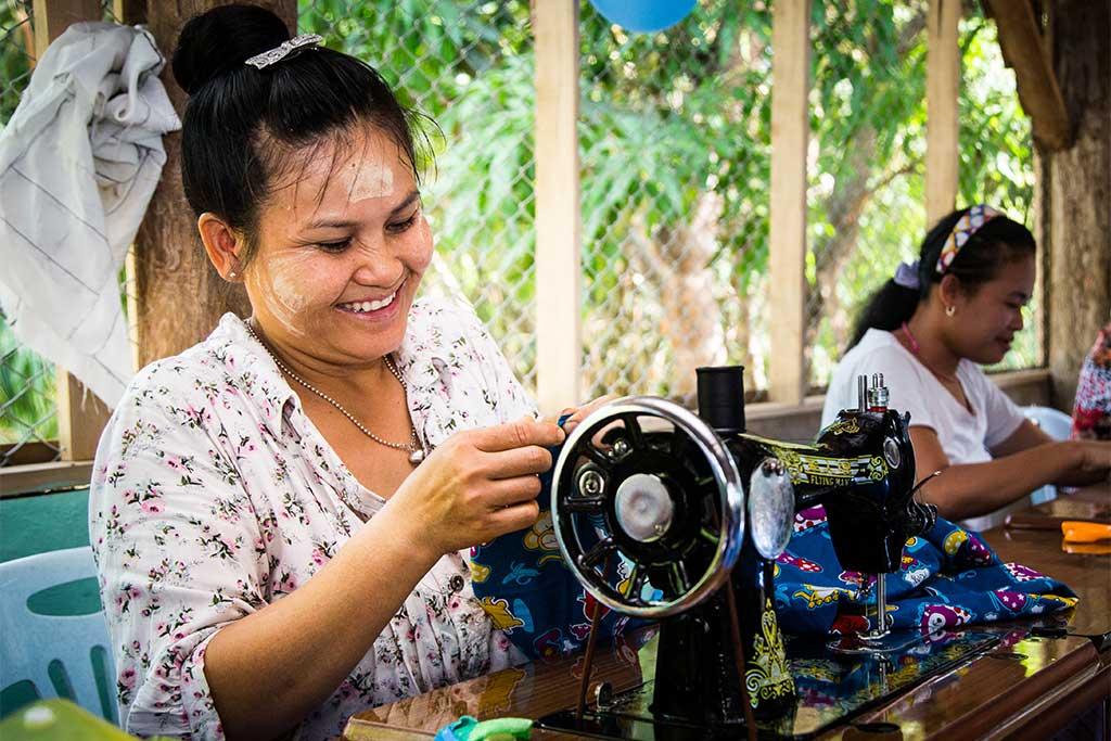 A woman sews colourful cloth.