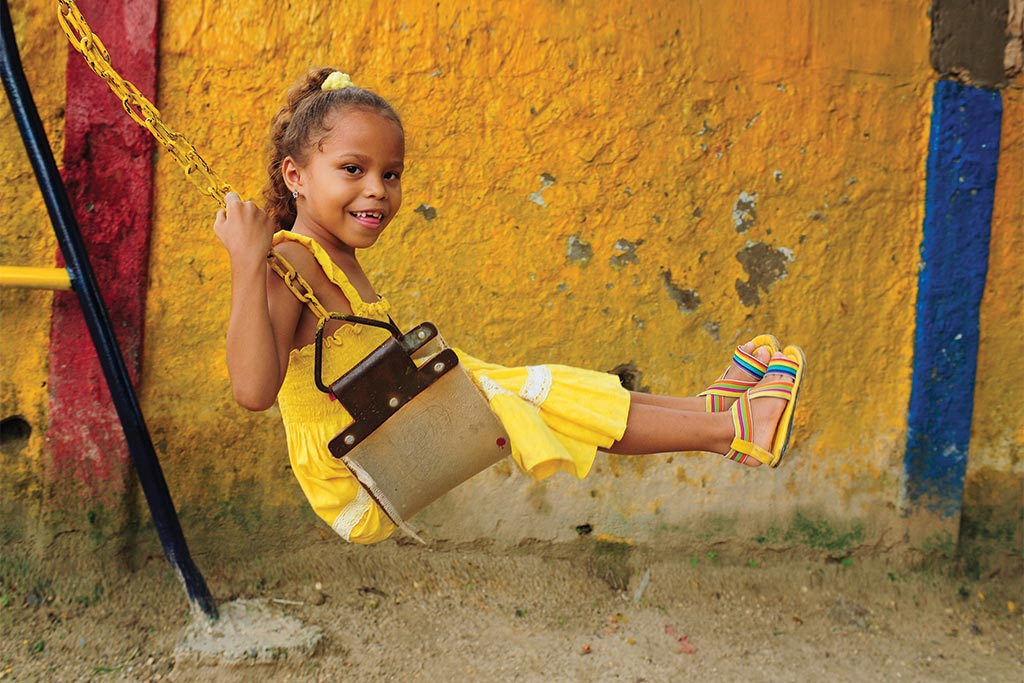 A girl in a yellow dress smiles as she swings on a swing.