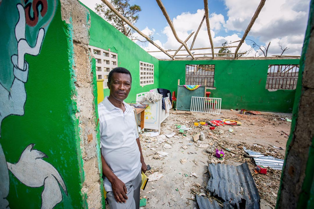 A Haitian man stands in the doorway of his storm-damaged house. Its walls are painted green, inside and out, it's roof is missing and the interior is strewn with leaves and garbage from the storm.