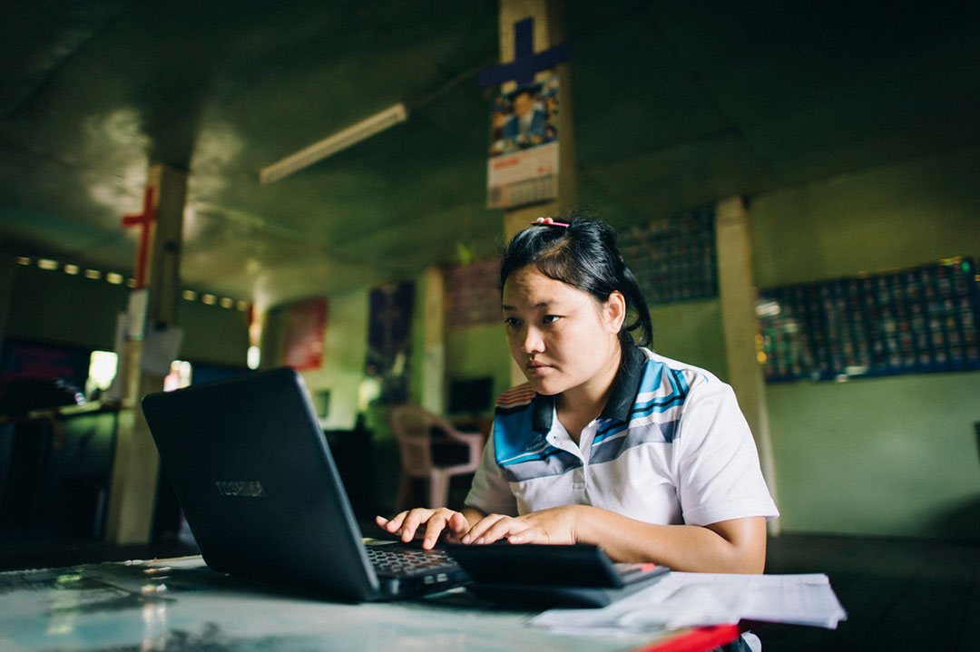 An asian woman sits in front of a black laptop, looking at the screen and typing. She's wearing blue and white, coloured t-shirt.