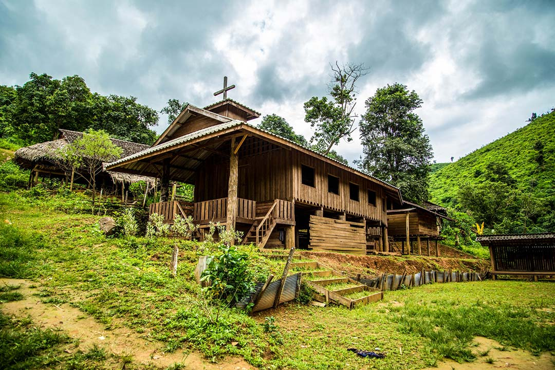 A church in Thailand stands on the side of a hill amidst lush green grass and trees. It is made out of wood and stands above the ground on wooden stilts.