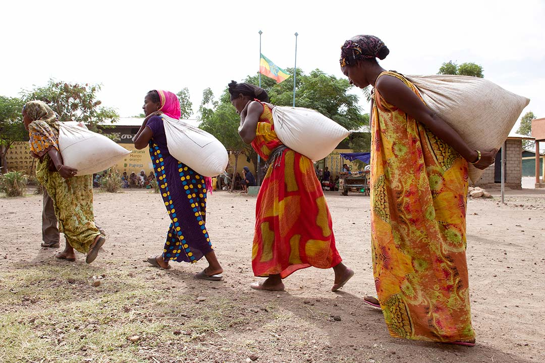 Ethiopian women wearing colourful, full length dresses, carry bags of rice across a dirt square.
