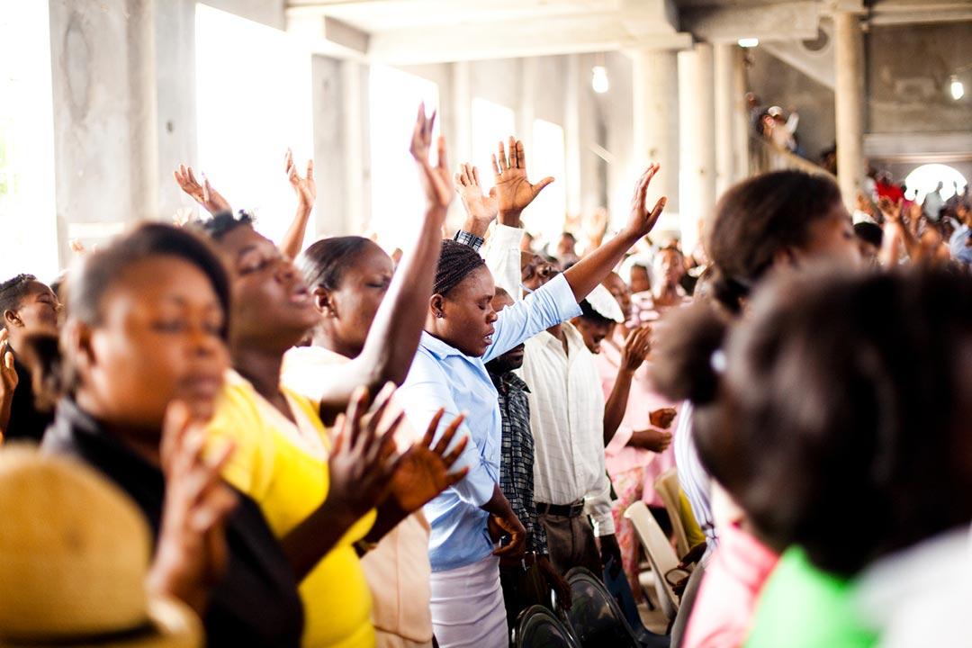 Women stand in an open air church building. They are worshiping with their eyes closed and their hands raised. They are surrounded by many other congregants.