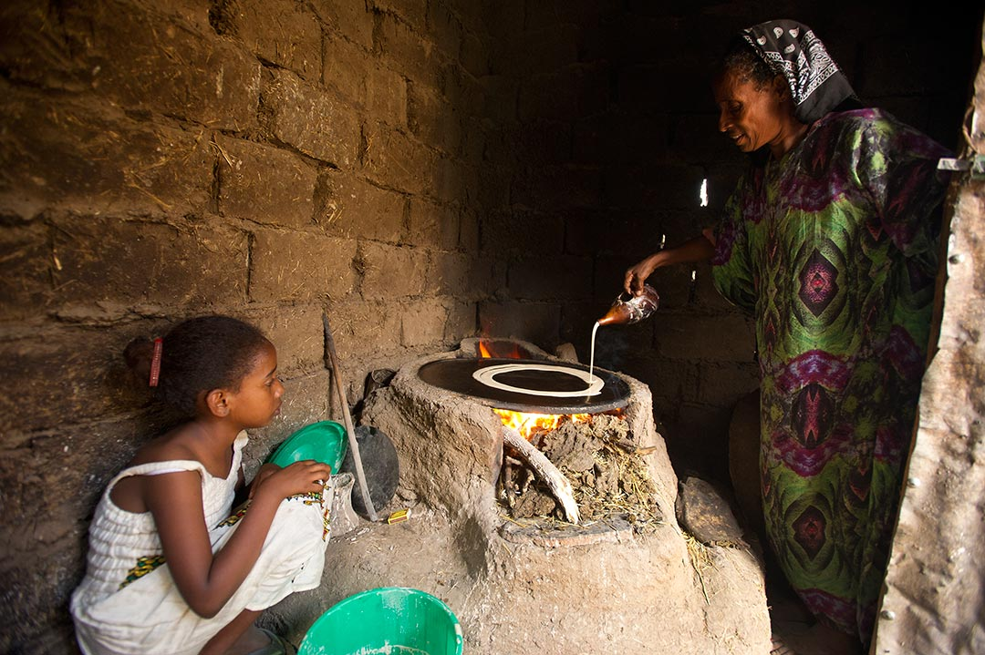 Blen, a young, Ethiopian girl in white dress, watches her grandma pour batter onto the family's stove to make injera, a spongy bread eaten with many meals in Ethiopia. They are in a small room with dirt floors and grey, brick walls
