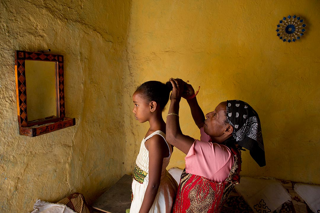 A girl and her mother stand in a yellow, stone walled room, looking into a small, wall mounted mirror. The mother stands behind the girl and does her hair.