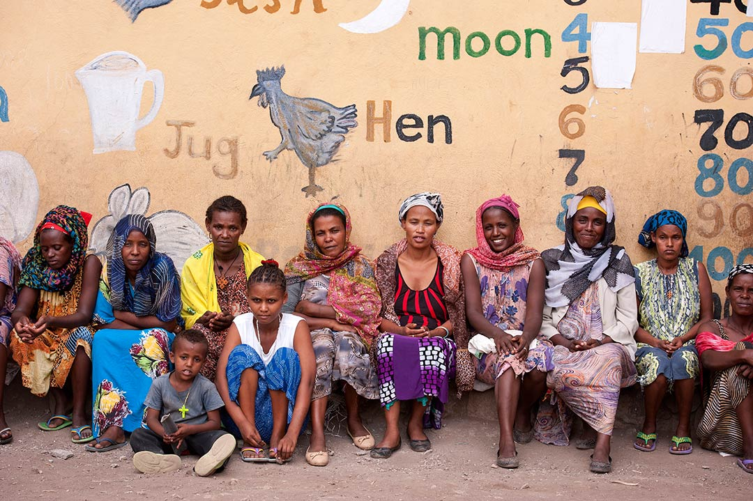 Ethiopian children wait outside one of Compassions development centres. The sit in front of a wall with illustrations, words and numbers painted on it.