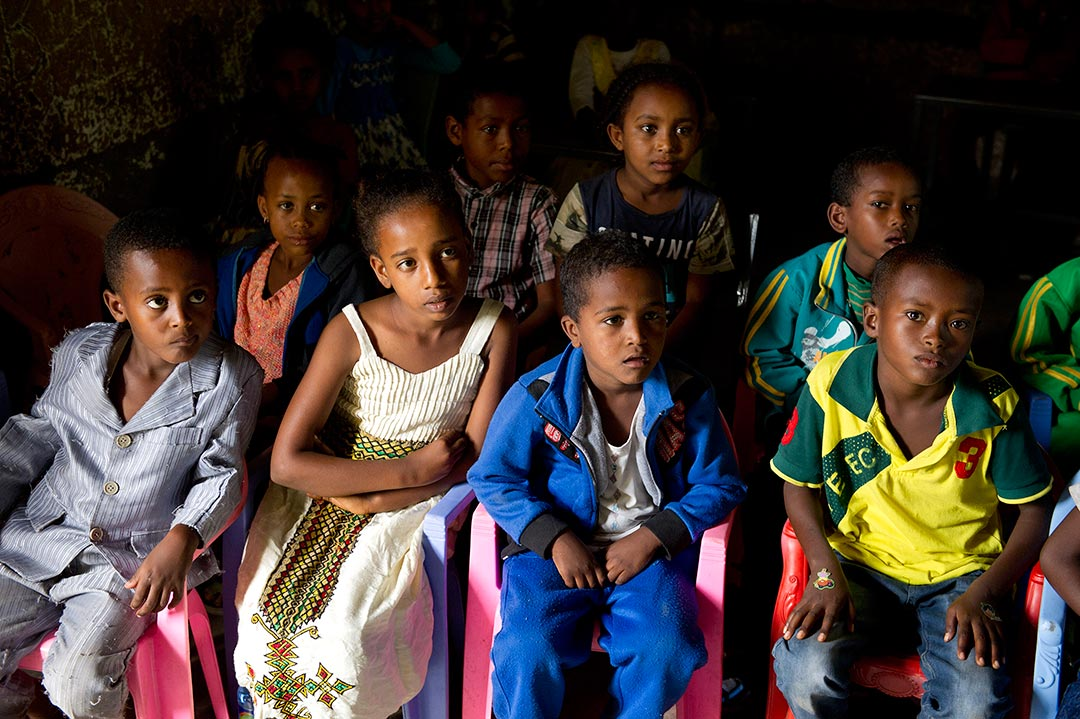Ethiopian children sit in small, plastic lawn chairs in a dark room. They look past the camera and listen to someone speaking to them.