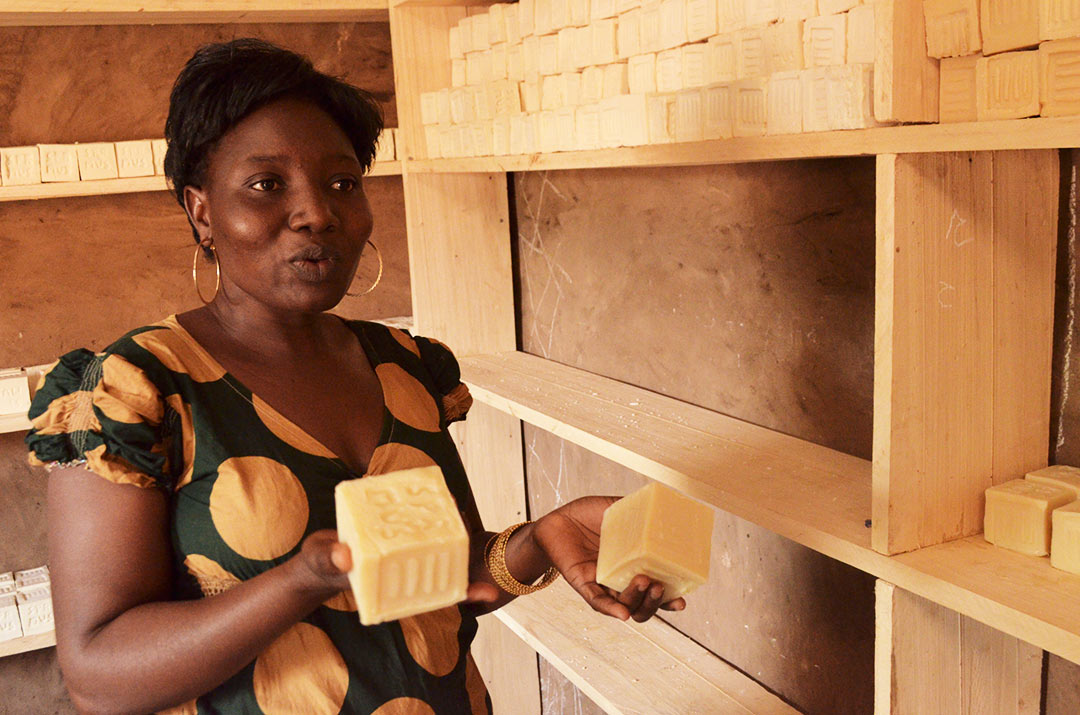An adult woman, wearing a brown and black dress, looks up and poses holding the soap for sale on the shelves, participating in learning and vocational skills program at the center, mothers, parents. She is looking off to the side, holding two big blocks of soap, one in each hand.