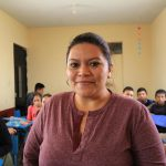 Leticia Judith Ochoa Contreras, adult woman, wearing a pink shirt stands in front of a group of boys and girls, teenagers, youth, teens, in a classroom, class, as a youth leader at church and the center, as a mentor and posing in a class portrait with her students behind her sitting at their desks, mentoring.