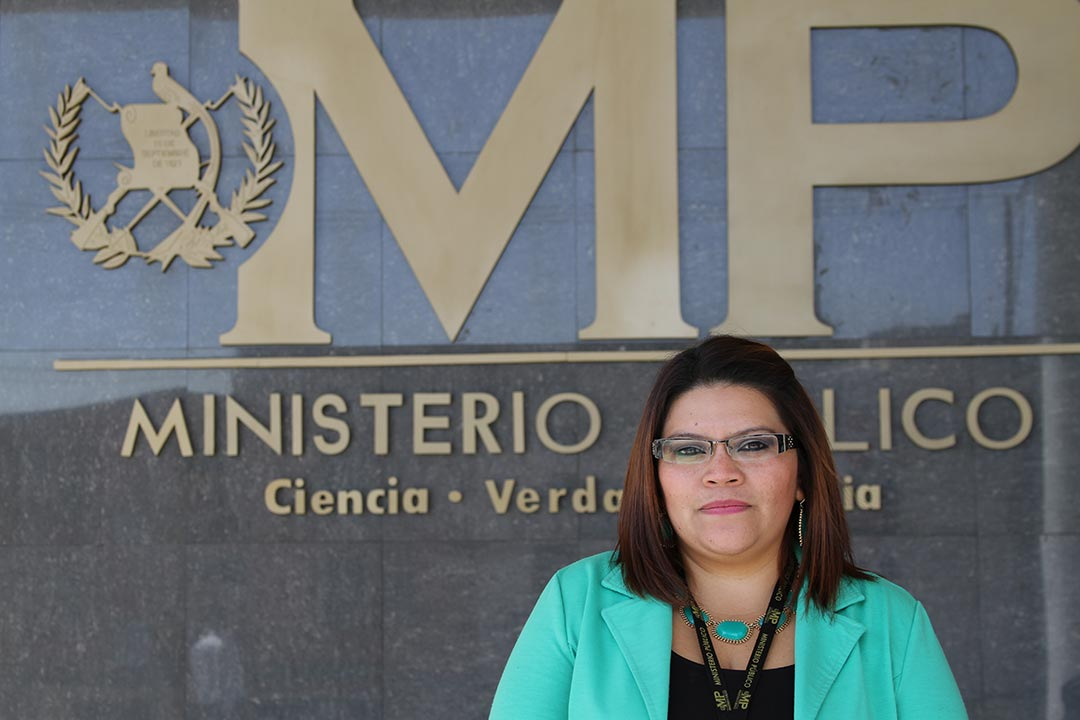 "Leticia Judith Ochoa Contreras, adult woman, wearing a green shirt, glasses, works in the Public Prosecutor's Office in the Abuse Women and Children's area, and stands outside in a portrait close-up, ""Ministerio Público, Ciencia, Verdad y Justicia"" which means ""Public Prosecutor's Office, Science, Truth and Justice"""