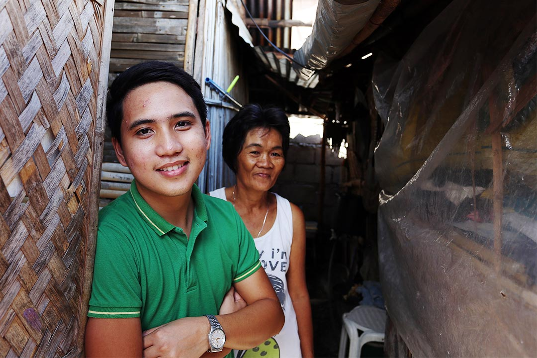 Jeric and his mother stand in front of their home in the Philippines. They are both smiling at the camera