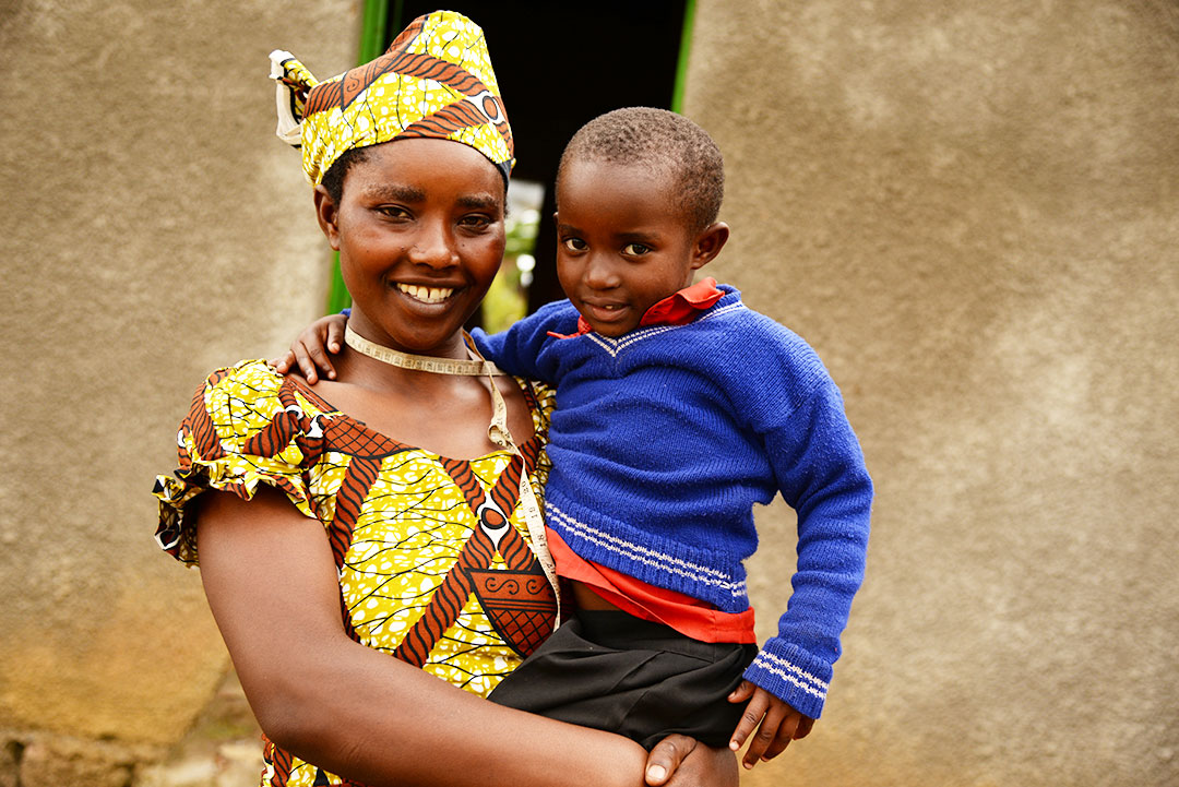Mukeshimana and her son stand infront of their three bedroom home.