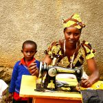 Mukeshimana and her son sit by a sewing machine. She is preparing to tailor a garment.
