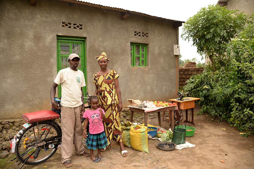 A Rwandan family stands beside the fruit stand, sewing machine and bicycle that they've used to gain an income and overcome poverty.