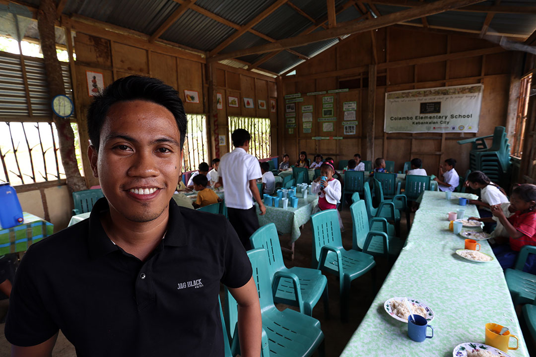 Mark stands in front of his classroom in the Philippines and smiles.