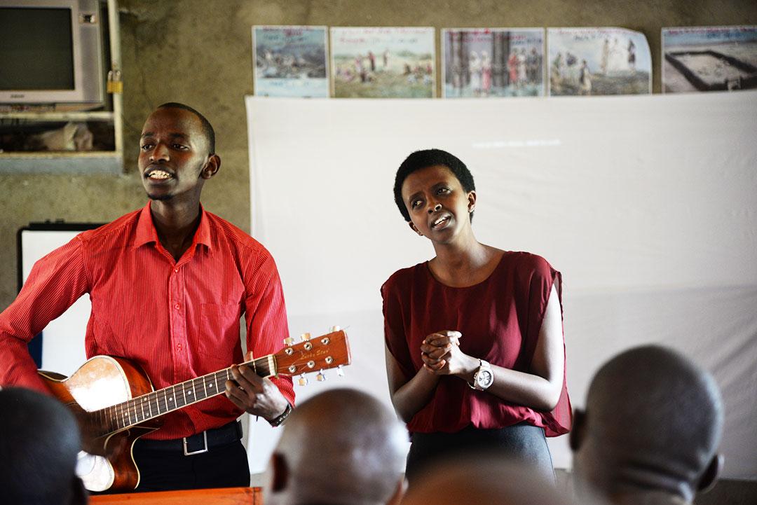 Bienvenue plays guitar and sings to a crowd.