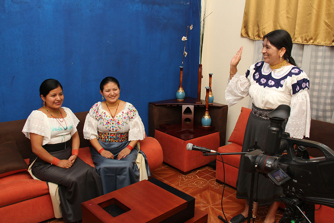 Two Ecuadorian women sit in front of a video camera as Viviane directs them.