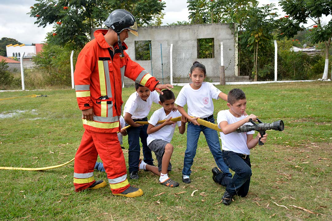 Jonathan, a Compassion graduate and firefighter, shows compassion children how to use a fire hose.