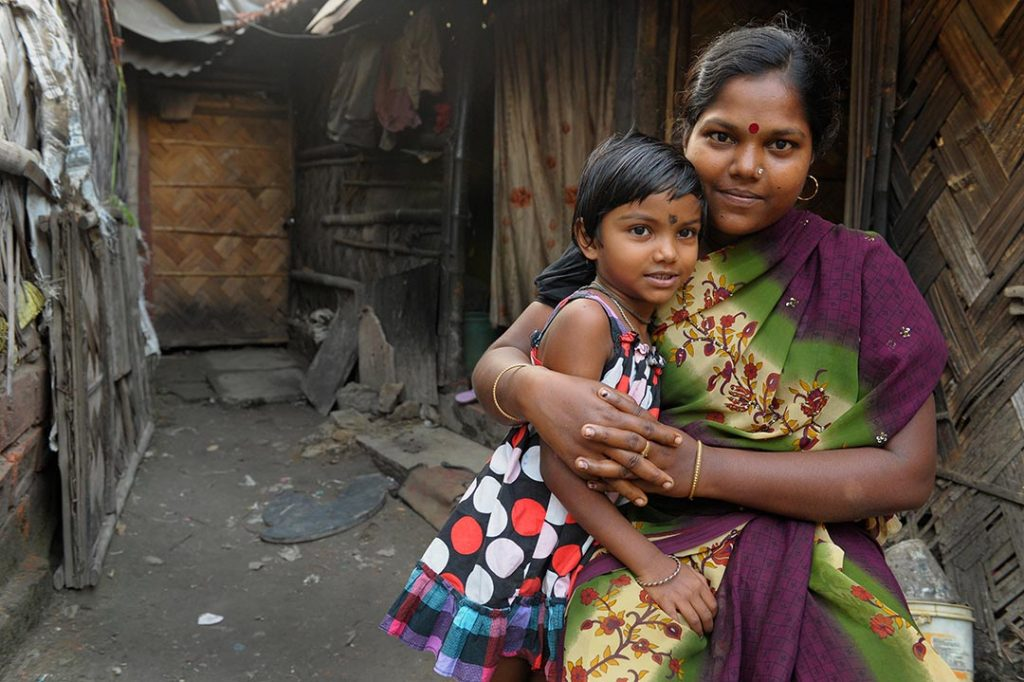 A young Indian girl is embraced by her mother. They sit in front there home which appears to be in a slum.