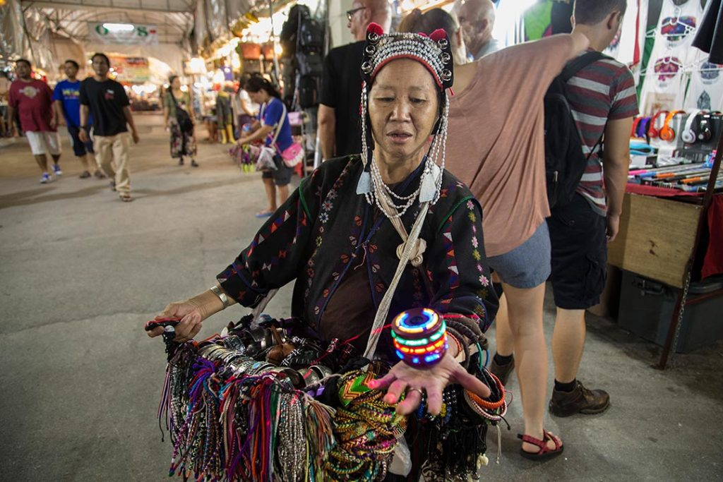 A woman dressed in traditional Thai garb sells trinkets at a Thai night market.