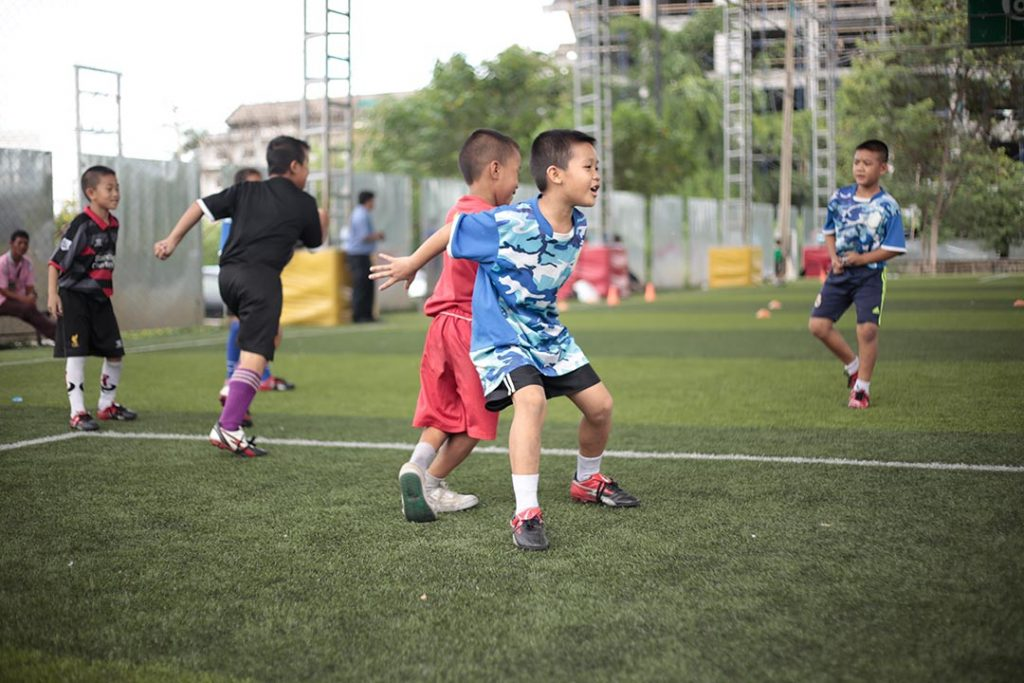 Two boys in soccer uniforms compete to receive a pass.