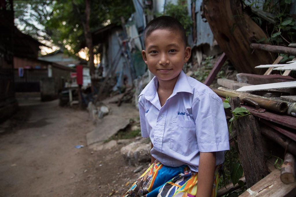 A Thai boy sits in front of a home in a village slum.
