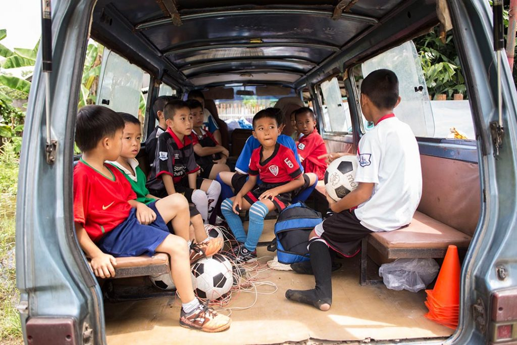 Young boys sit in the back of a van dressed in soccer uniforms, ready to play.