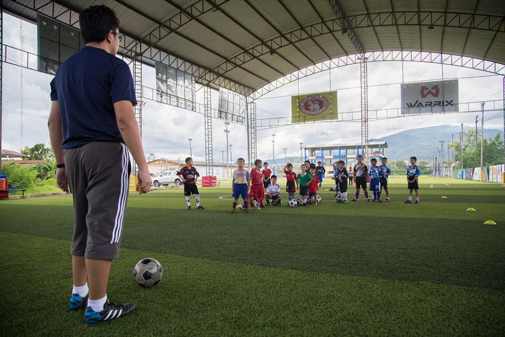 A soccer coach stands at the end of a covered soccer ball, preparing to kick the ball to his team.