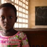 Aklobessi, a four year-old girl living in Togo, looks at the camera as she sits on a bench in a Compassion Centre. She's wearing a