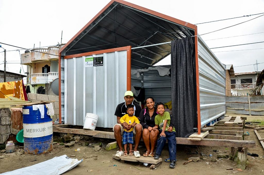 Dastin and his family sit in front of their new home. It's made of corrugated steel and stands on a wooden, raised platform.