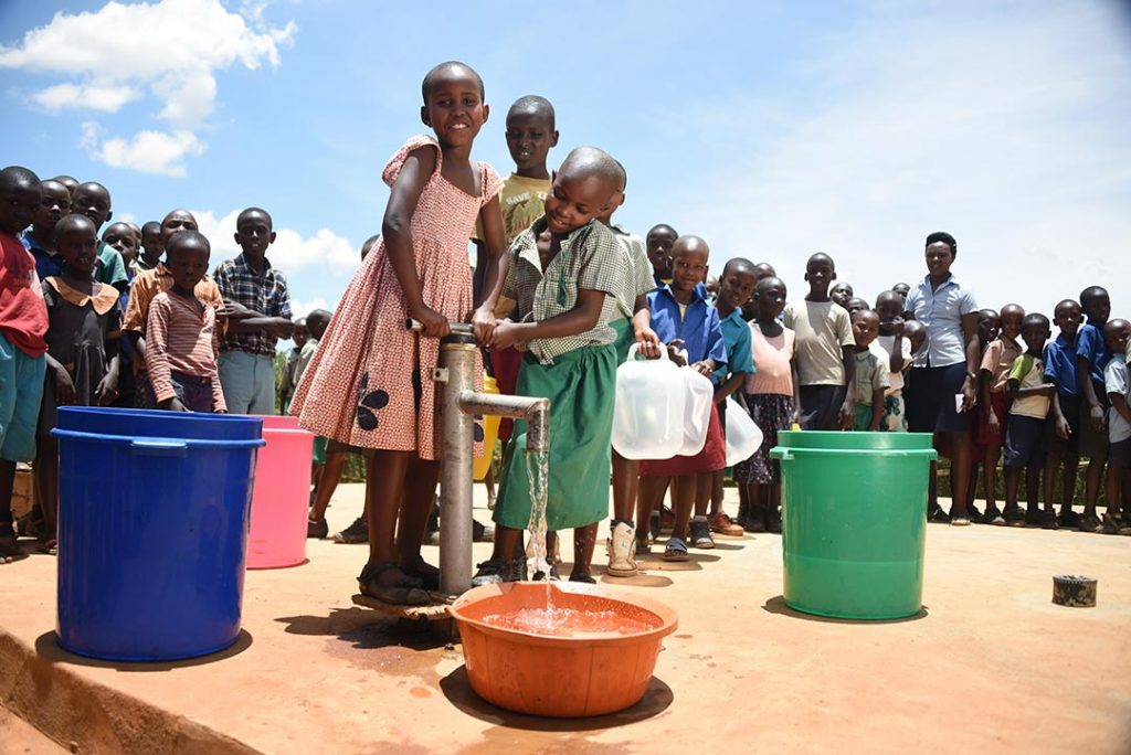 The water pump at Janet's Compassion centre. Janet and other children smile as they pump water into vessels.
