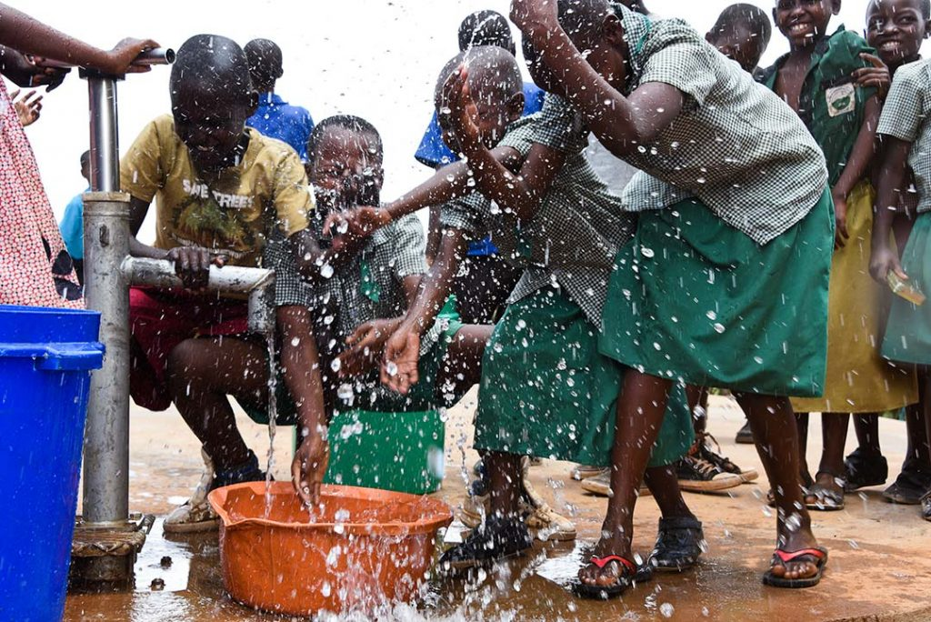 Children play at the well, splashing and laughing.