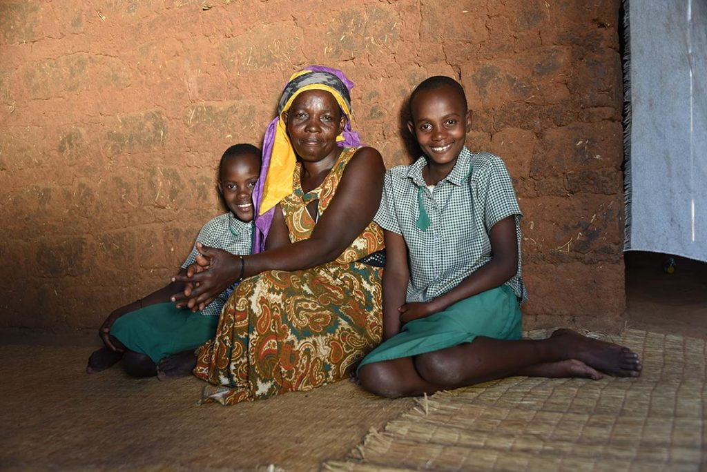 Janet sits with her mom and sister at their home in Rwanda