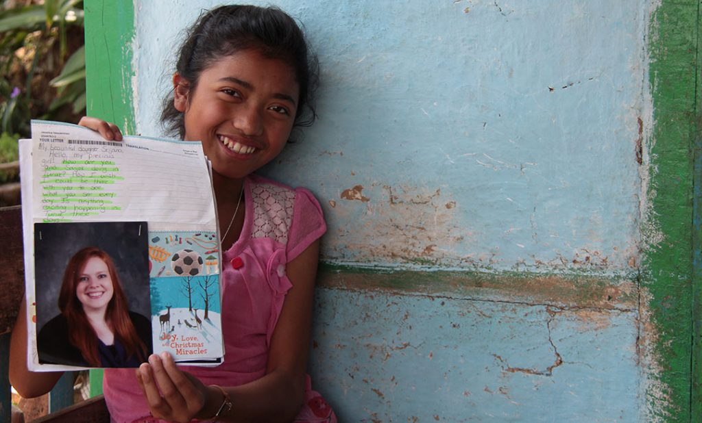 An Indian girl holds a letter up to show the camera. She smiles and leans against a blue wall
