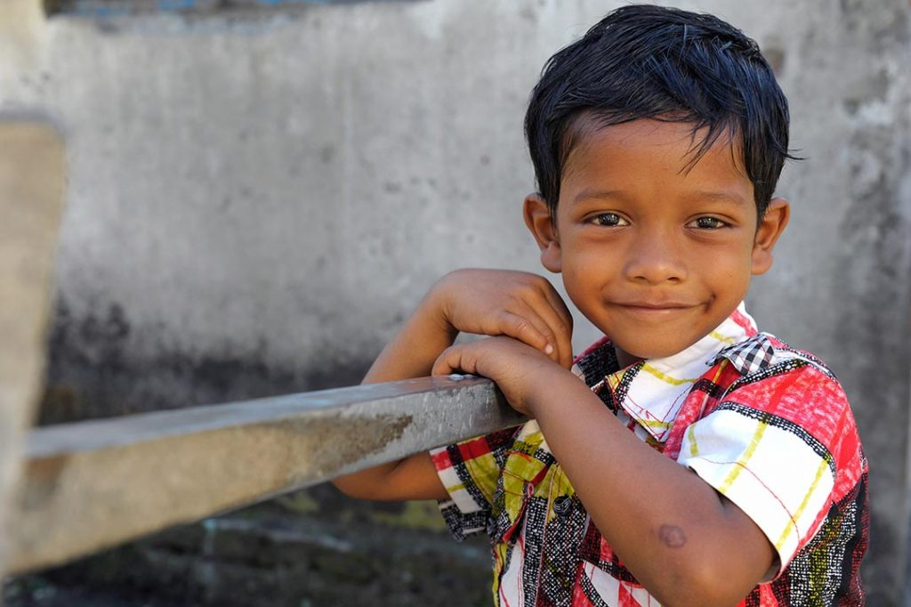 A boy leans on a rail and smiles at the camera.