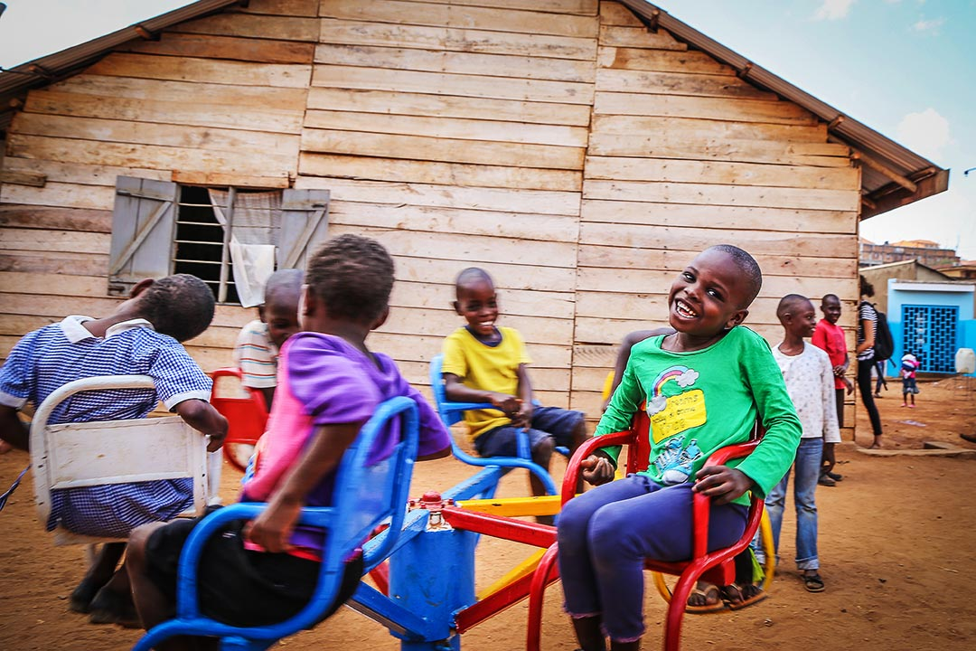 A group of children ride on a merry-go-round in front of their Compassion centre.