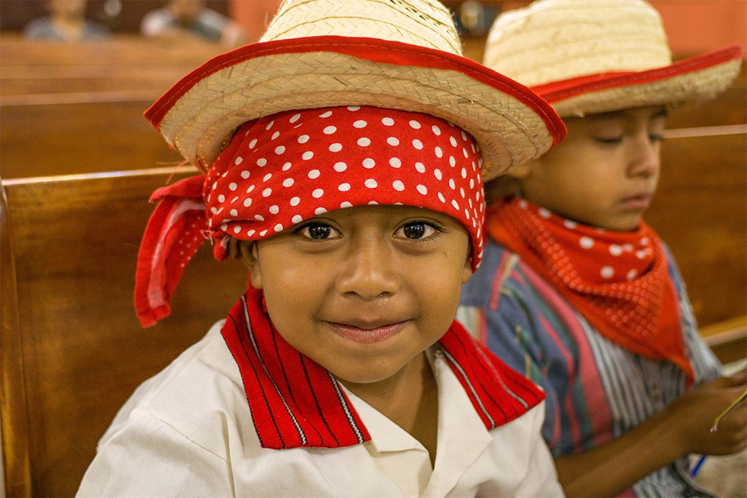 A young boy from Guatemala sits in a church pew. He's wearing straw hat on top of a red bandana. His white shirt has a striped, red collar.